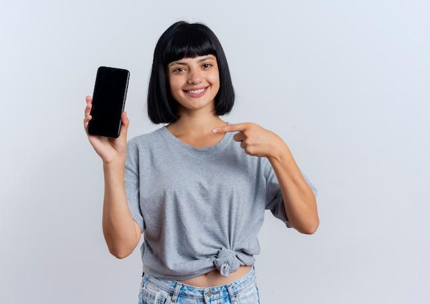 Het glimlachende jonge donkerbruine kaukasische meisje houdt en wijst op telefoon
