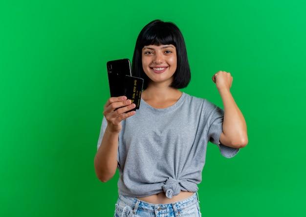 Het glimlachende jonge donkerbruine kaukasische meisje houdt telefoon en creditcard die vuist houden op groene achtergrond met exemplaarruimte wordt geïsoleerd