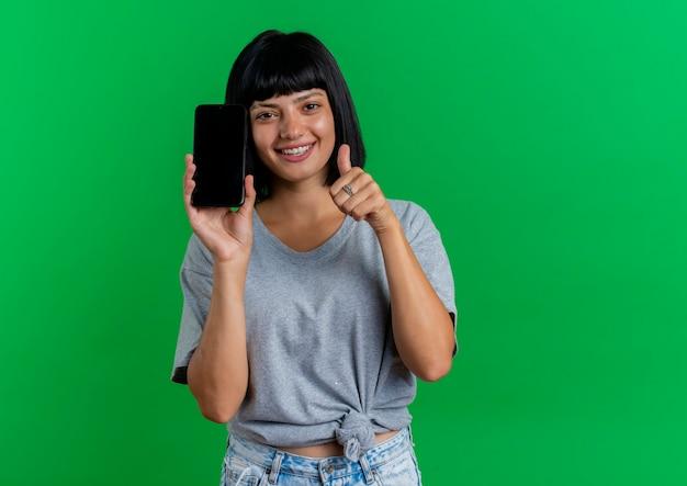 Het glimlachende jonge donkerbruine kaukasische meisje houdt telefoon en duimen omhoog geïsoleerd op groene achtergrond met exemplaarruimte