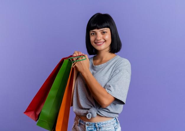 Het glimlachende jonge donkerbruine kaukasische meisje houdt veelkleurige boodschappentassen