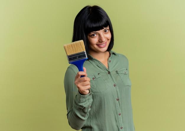 Het glimlachende jonge donkerbruine kaukasische meisje houdt verfborstel die camera bekijkt die op olijfgroene achtergrond met exemplaarruimte wordt geïsoleerd
