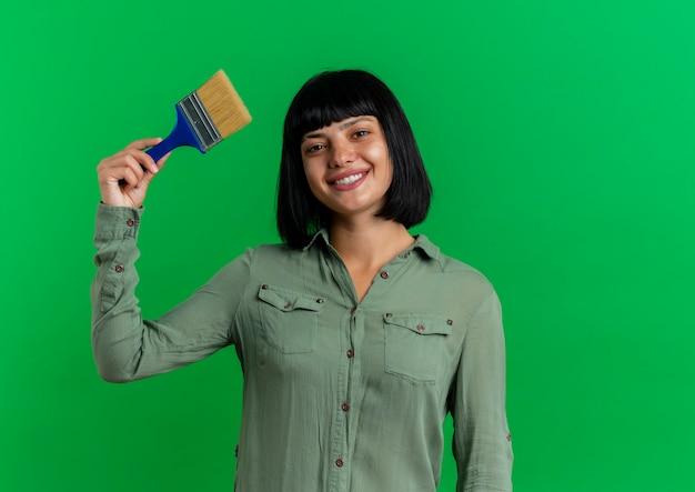 Het glimlachende jonge donkerbruine kaukasische meisje houdt verfborstel die op groene achtergrond met exemplaarruimte wordt geïsoleerd