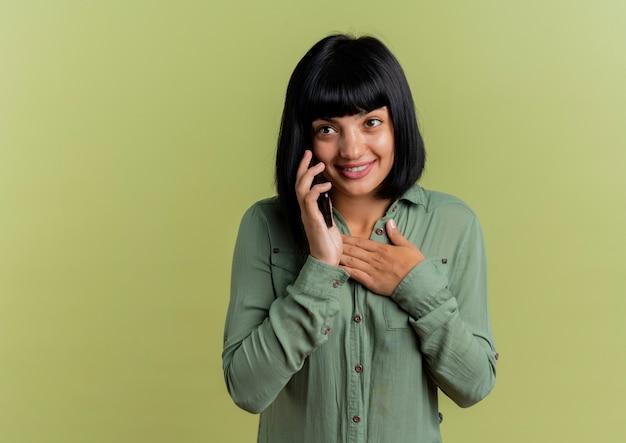Het glimlachende jonge donkerbruine kaukasische meisje legt hand op borst die op telefoon spreekt