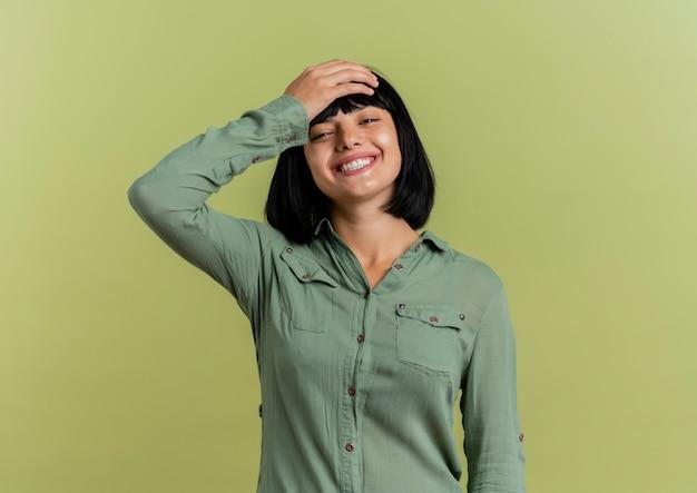 Het glimlachende jonge donkerbruine kaukasische meisje legt hand op hoofd die camera bekijkt die op olijfgroene achtergrond met exemplaarruimte wordt geïsoleerd