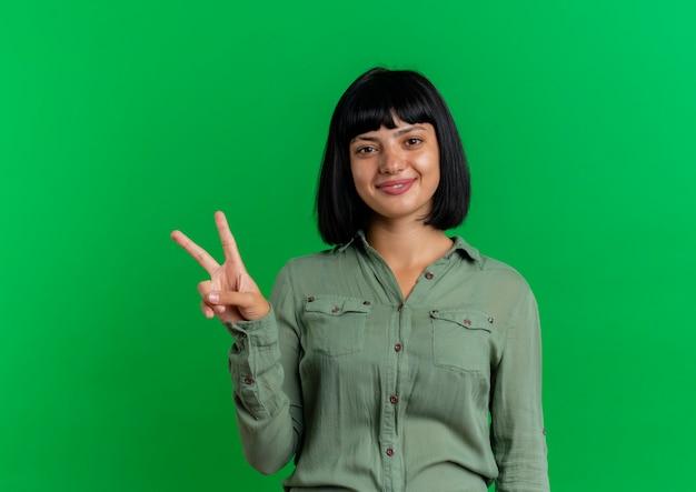 Het glimlachende jonge donkerbruine kaukasische teken van de de overwinninghand van meisjesgebaren dat op groene achtergrond met exemplaarruimte wordt geïsoleerd