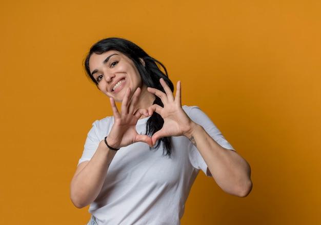 Het glimlachende jonge donkerbruine kaukasische teken van de het harthand van meisjesgebaren dat op oranje muur wordt geïsoleerd