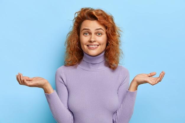 Het glimlachende jonge gemberwijfje maakt vragend gebaar, spreidt handen zijwaarts uit
