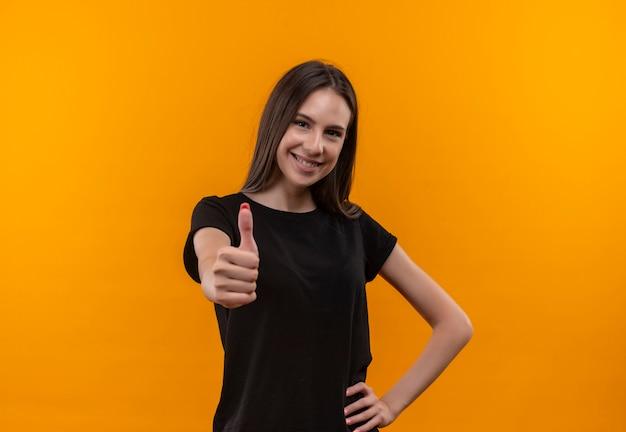 Het glimlachende jonge kaukasische meisje dat zwarte t-shirt draagt haar duim omhoog legde hand op heup op geïsoleerde oranje achtergrond