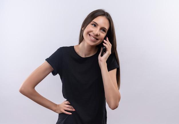 Het glimlachende jonge kaukasische meisje dat zwarte t-shirt draagt spreekt aan telefoon legde haar hand op heup op geïsoleerde witte achtergrond