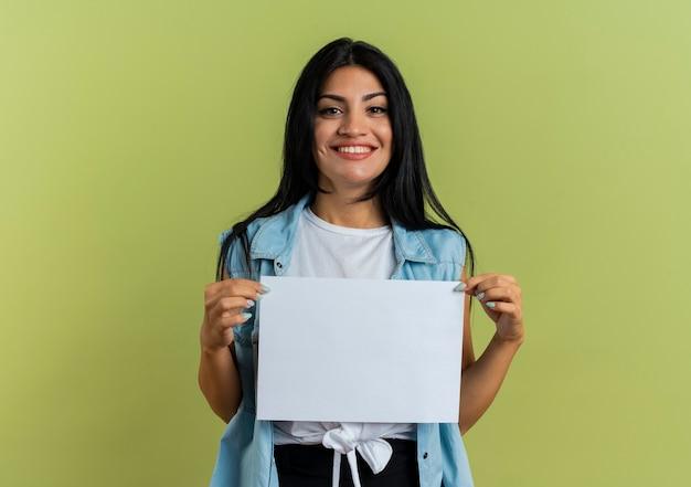 Het glimlachende jonge kaukasische meisje houdt document blad