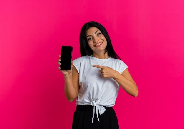 Het glimlachende jonge kaukasische meisje houdt en wijst op telefoon