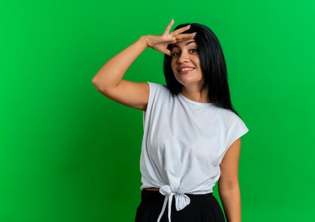 Het glimlachende jonge kaukasische meisje houdt palm bij voorhoofd het kijken