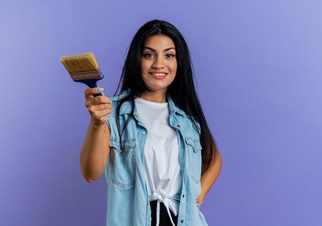 Het glimlachende jonge kaukasische meisje houdt verfborstel die op purpere achtergrond met exemplaarruimte wordt geïsoleerd