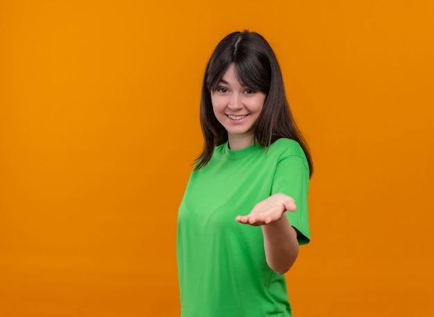 Het glimlachende jonge kaukasische meisje in groen overhemd toont lege hand aan camera op geïsoleerde oranje achtergrond met exemplaarruimte