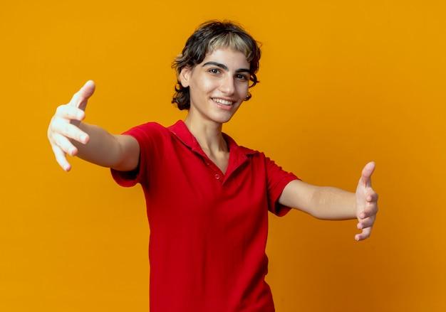 Het glimlachende jonge kaukasische meisje met pixiekapsel beweert iets te houden dat op oranje achtergrond wordt geïsoleerd