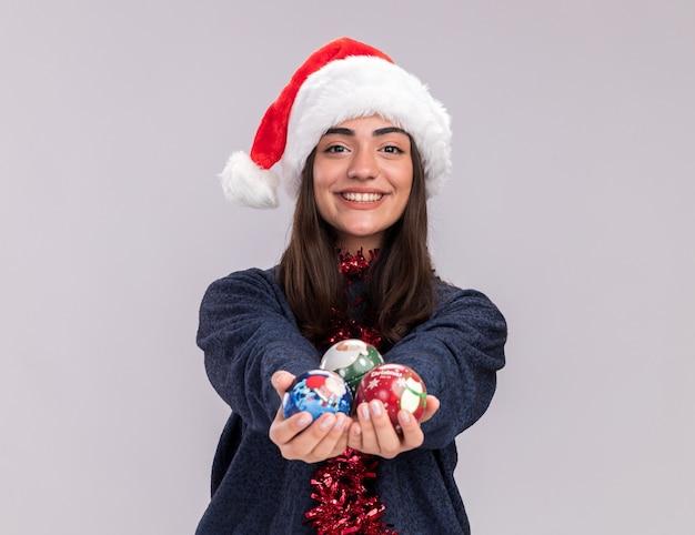 Het glimlachende jonge kaukasische meisje met santahoed en slinger om hals houdt glasbalornamenten