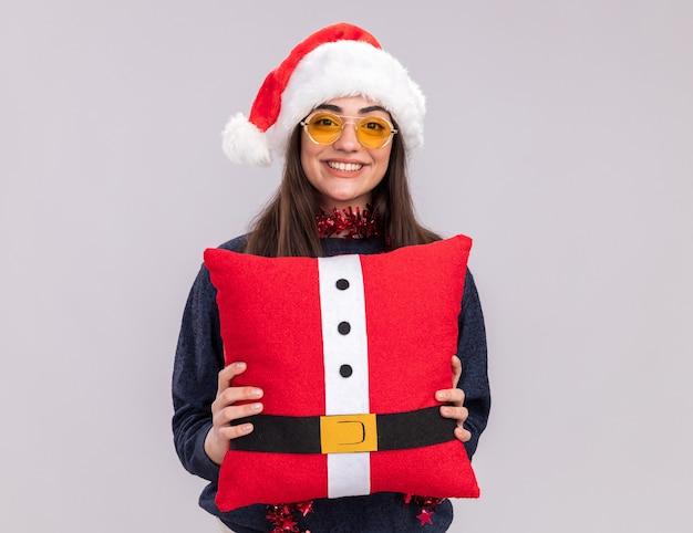 Het glimlachende jonge kaukasische meisje met santahoed en slinger om hals houdt verfraaid hoofdkussen