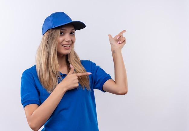 Het glimlachende jonge leveringsmeisje die blauw uniform en glb dragen wijst naar kant die op witte muur met exemplaarruimte wordt geïsoleerd