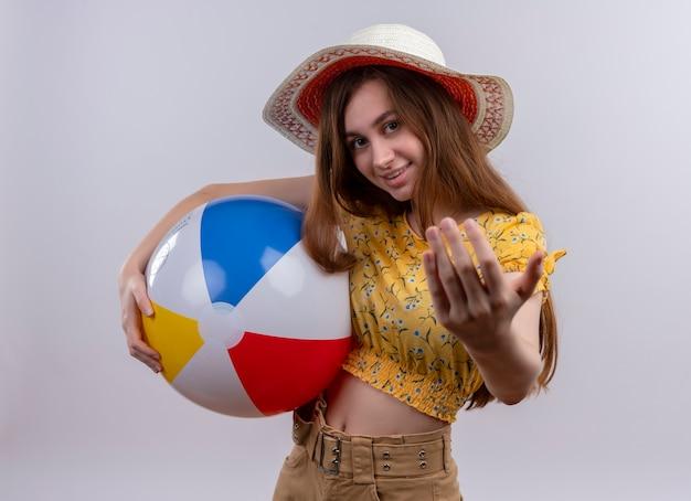 Het glimlachende jonge meisje dat het strandbal van de hoedholding draagt ?? komt hier gebaar op geïsoleerde witte muur