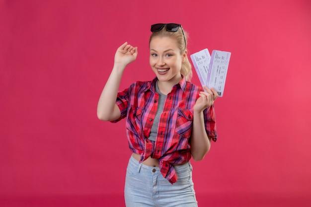 Het glimlachende jonge meisje dat van de reiziger een rood overhemd in glazen draagt die kaartjes houdt toont grootte op geïsoleerde roze achtergrond