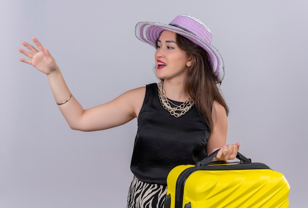 Het glimlachende jonge meisje dat van de reiziger zwart onderhemd draagt in de koffer van de hoedenholding en wijst naar weg op witte achtergrond