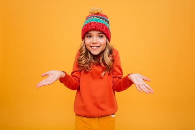 Het glimlachende jonge meisje in sweater en hoed haalt haar schouders op en bekijkt de camera over sinaasappel