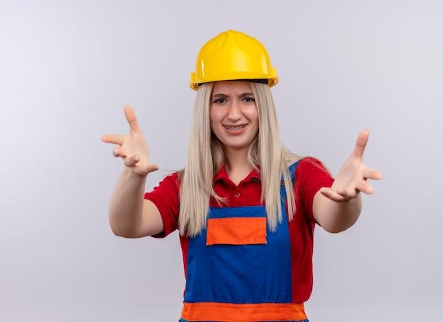 Het glimlachende jonge meisje van de blonde ingenieurbouwer in uniform in tandsteunen die uit handen op geïsoleerde witte ruimte strekken