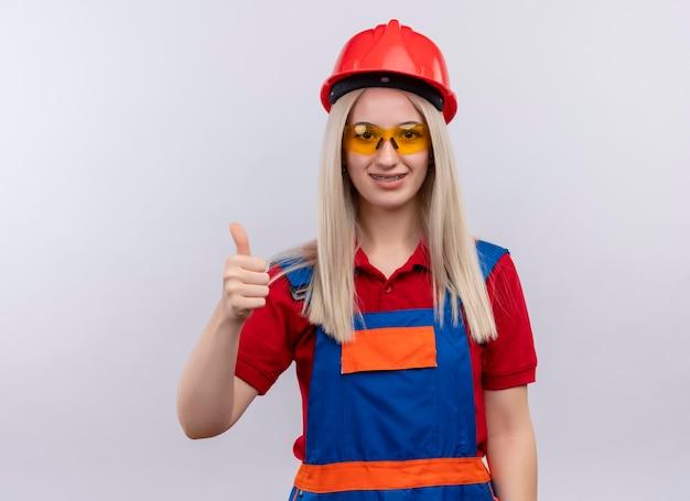Het glimlachende jonge meisje van de blonde ingenieurbouwer in uniform in tandsteunen die veiligheidsbril dragen die duim op geïsoleerde witte ruimte met exemplaarruimte tonen