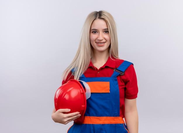 Het glimlachende jonge meisje van de blonde ingenieurbouwer in uniform in tandsteunen die veiligheidshelm op geïsoleerde witte ruimte met exemplaarruimte houden