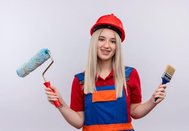 Het glimlachende jonge meisje van de blonde ingenieurbouwer in uniform in tandsteunen die verfroller en kwast op geïsoleerde witte ruimte houden