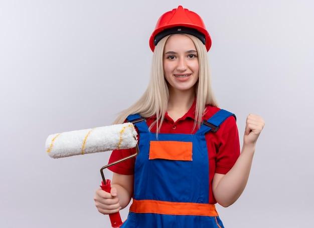 Het glimlachende jonge meisje van de blonde ingenieurbouwer in uniform in tandsteunen die verfroller houden en vuist opheffen op geïsoleerde witte ruimte
