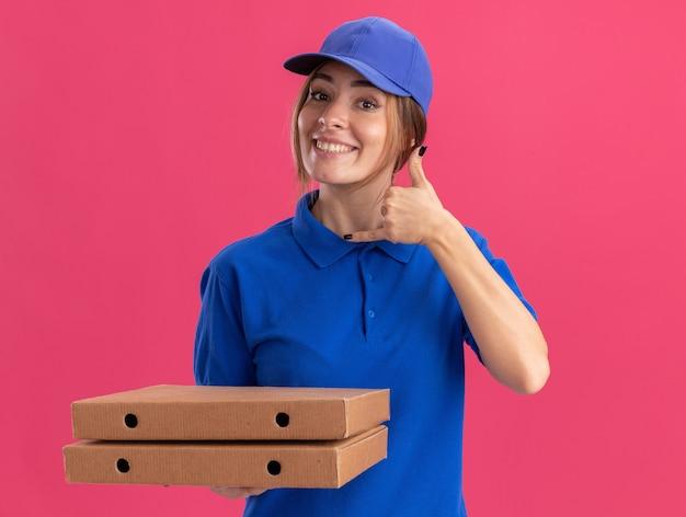 Het glimlachende jonge mooie bezorgmeisje in uniforme gebaren hangt los en houdt pizzadozen op roze