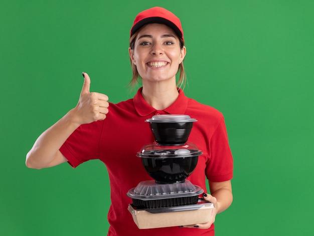 Het glimlachende jonge mooie leveringsmeisje in uniform beduimelt omhoog en houdt voedselcontainers op groen