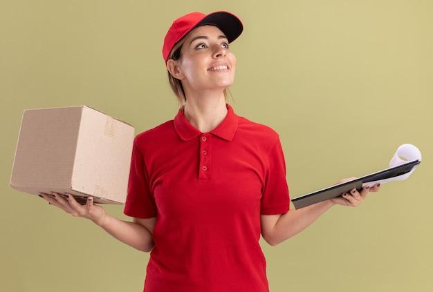 Het glimlachende jonge mooie leveringsmeisje in uniform houdt klembord en kartondoos die kant op olijfgroen bekijkt