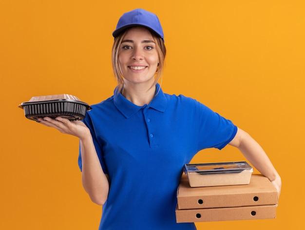 Het glimlachende jonge mooie leveringsmeisje in uniform houdt papieren voedselpakketten en containers op pizzadozen op oranje