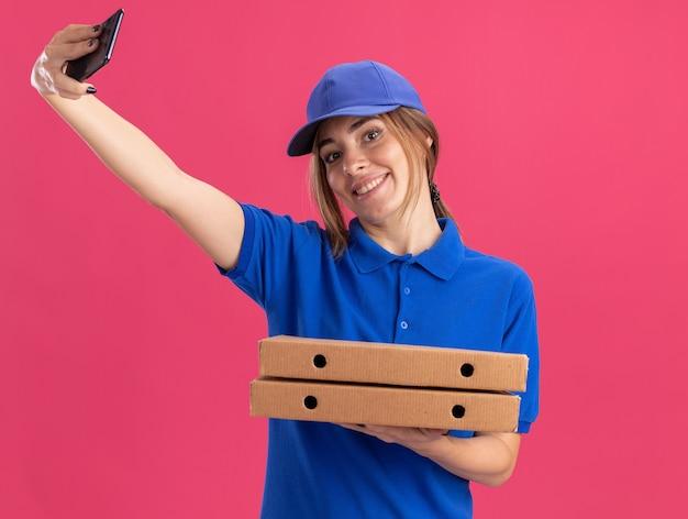 Het glimlachende jonge mooie leveringsmeisje in uniform houdt pizzadozen en telefoon op roze