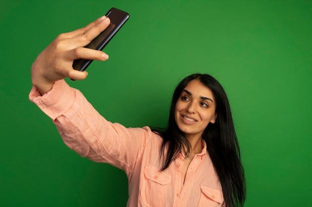 Het glimlachende jonge mooie meisje dat roze t-shirt draagt, neemt een selfie die op groene muur wordt geïsoleerd