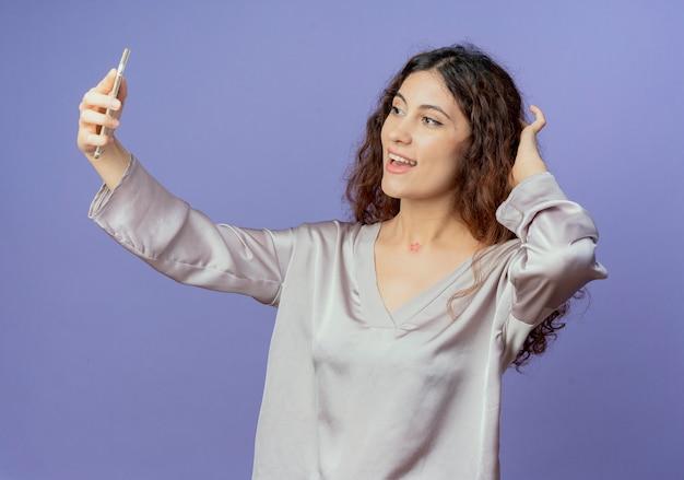 Het glimlachende jonge mooie meisje neemt een selfie en zet hand op hoofd geïsoleerd op blauw