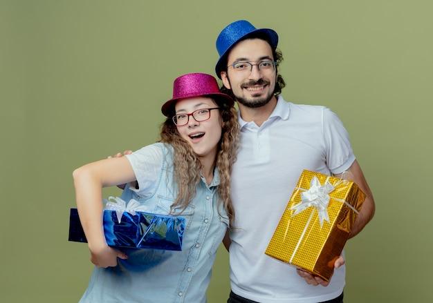 Het glimlachende jonge paar die roze en blauwe hoed dragen omhelzen elkaar en houden giftdozen die op olijfgroene muur worden geïsoleerd