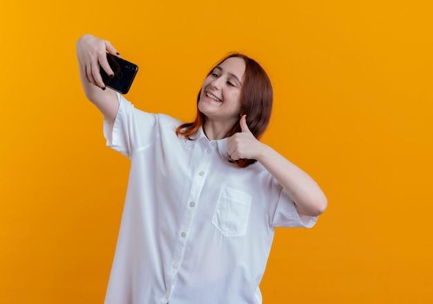 Het glimlachende jonge roodharige meisje neemt een selfie en haar duim omhoog geïsoleerd op geel