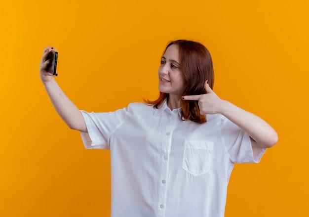 Het glimlachende jonge roodharige meisje neemt een selfie en wijst op telefoon die op gele achtergrond wordt geïsoleerd