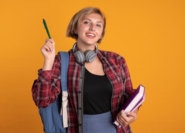 Het glimlachende jonge slavische studentenmeisje met hoofdtelefoons die rugzak dragen houdt penboek en notitieboekje