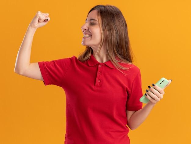 Het glimlachende jonge vrij kaukasische meisje houdt vuist en houdt telefoon op sinaasappel