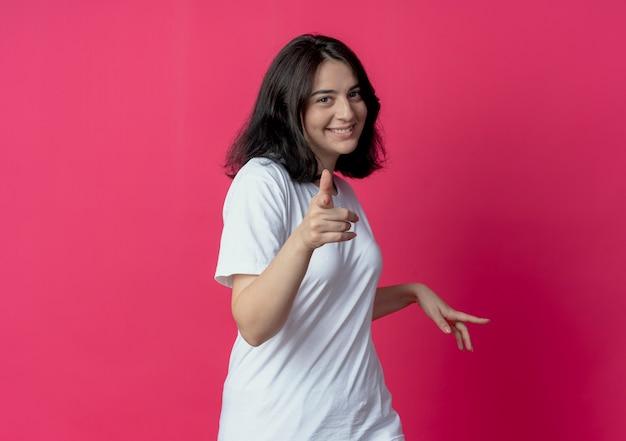 Het glimlachende jonge vrij kaukasische meisje richtend op camera en houdt hand in lucht die op karmozijnrode achtergrond met exemplaarruimte wordt geïsoleerd