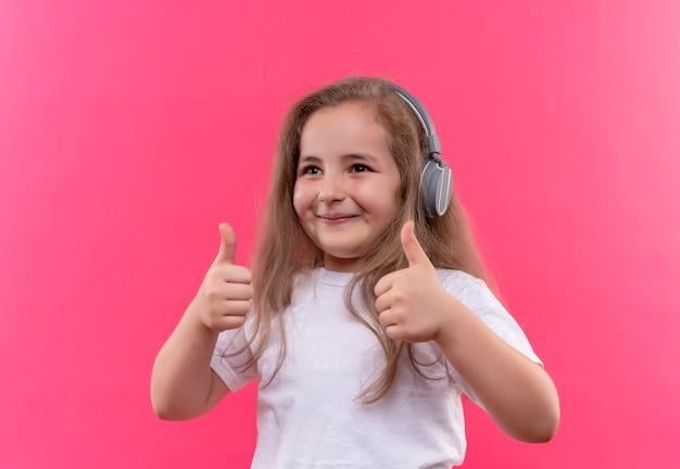 Het glimlachende kleine schoolmeisje die witte t-shirt dragen luistert muziek op hoofdtelefoons haar duimen omhoog op geïsoleerde roze achtergrond