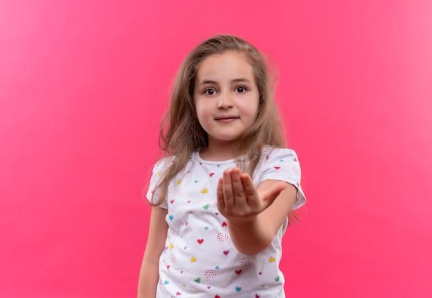 Het glimlachende kleine schoolmeisje die witte t-shirt dragen stak hand op geïsoleerde roze achtergrond uit