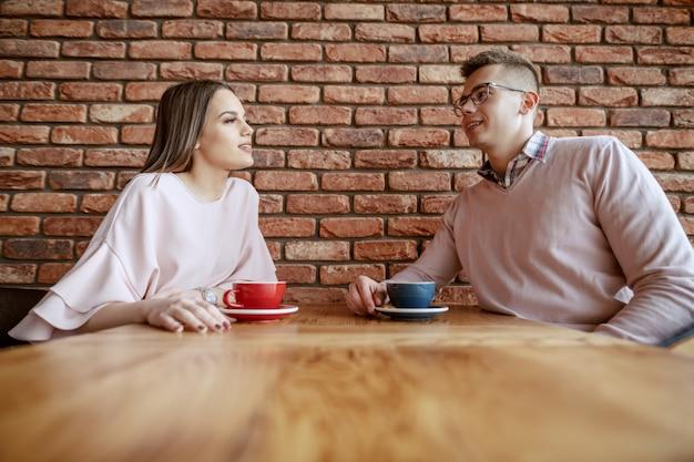 Het glimlachende leuke paar kleedde het elegante babbelen en het drinken van koffie in cafetaria