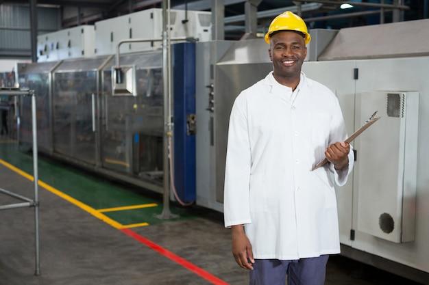 Het glimlachende mannelijke klembord van de arbeidersholding in magazijn