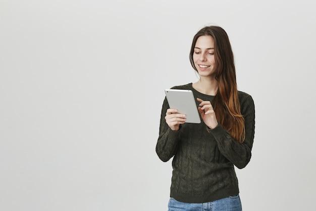 Het glimlachende meisje dat digitale tablet gebruikt, bewerkt beeld in app