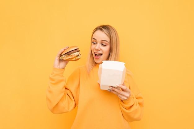 Het glimlachende meisje dat oranje kleren draagt is verpakt met een hamburger in zijn handen op een geel